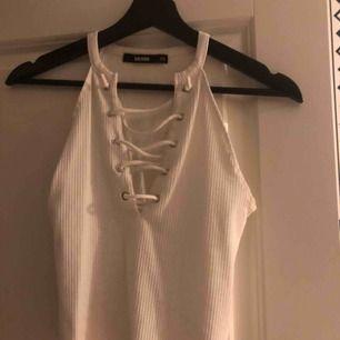Ett fint vitt linne från bikbok i storlek XS. Har snörning vilket är en fin detalj på det hela. Använd men fint skick. Frakt kan tillkomma