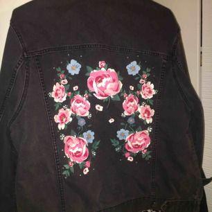 En svart jeansjacka med rosor och lite pärlor på! den är från HM och är aldrig använd. För mig som brukar ha S så är det som en oversize jacka, perfekt till våren! Säljer den för att den inte kommer till användning. Frakten betalar köparen