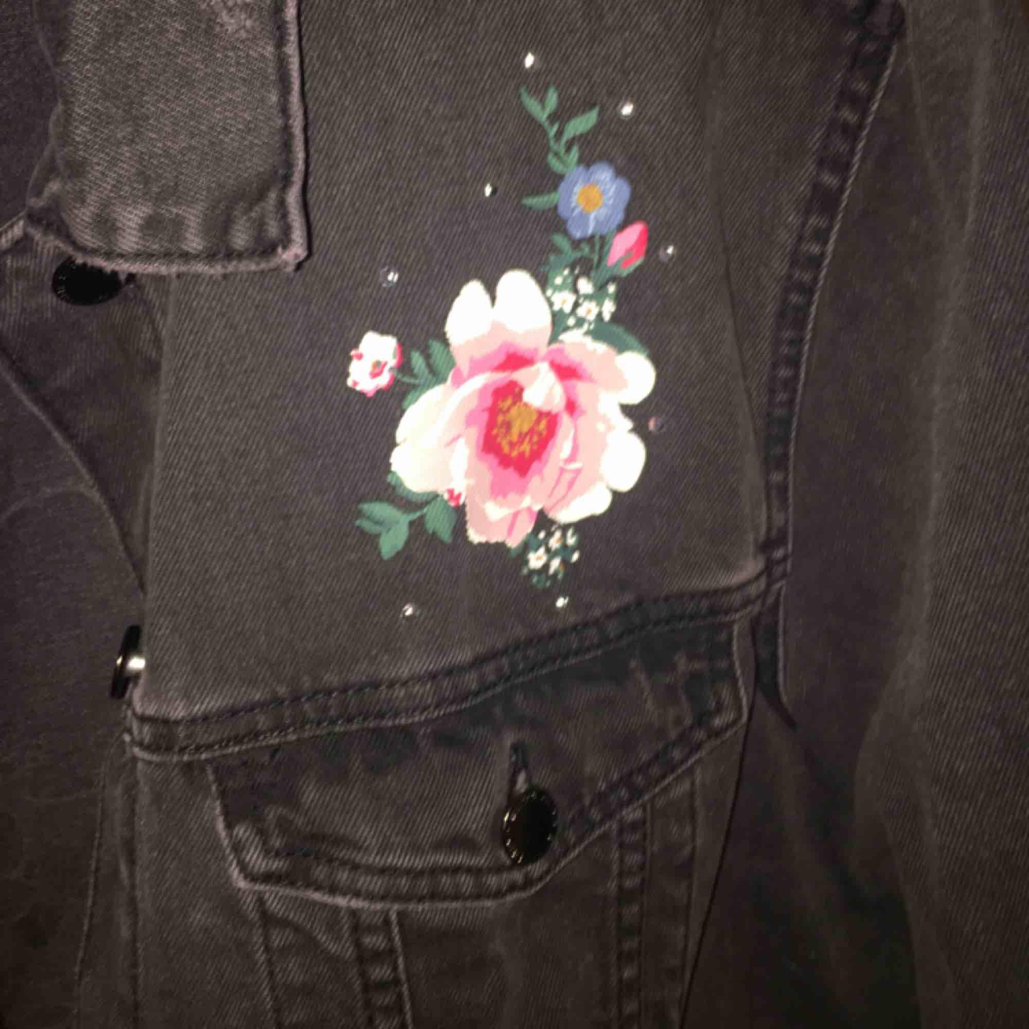 En svart jeansjacka med rosor och lite pärlor på! den är från HM och är aldrig använd. För mig som brukar ha S så är det som en oversize jacka, perfekt till våren! Säljer den för att den inte kommer till användning. Frakten betalar köparen. Jackor.