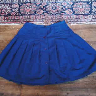 Kornblå kjol från 60talet. Märkt 38 är som en Xs/34/36. Bredd midja 33cm längd 44cm. 100kr plus frakt 36kr