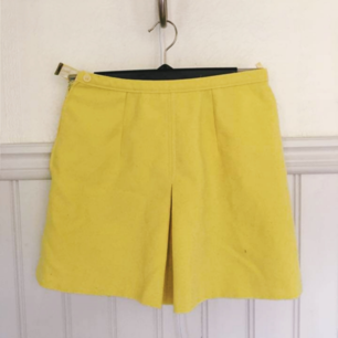 Liten gul kjol från 60talet. Den gula färgen är svår att få rättvis på bild, men den är pyttelite ljusare än på denna bild. Har två små fickor bak. Uppskattas till xs/34/36 Bredd 33cm längd 39cm 120kr plus frakt 36kr