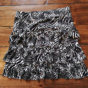 Cool kjol i zebramönster. Märkt stl L. Resår i midjan så kan passa olika stora. Bredd midja 40cm längd 47cm 50kr plus frakt 39kr