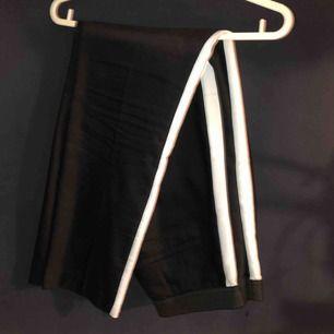 Svarta kostymbyxor med vita streck på sidan från Zara! Lite slitage i sömmen i midjan men går lätt att sy ihop!