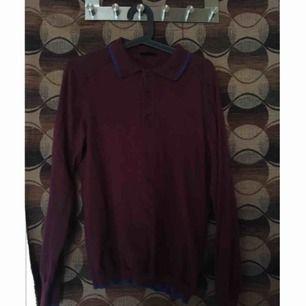 Mysig stickad tröja med krage och mörkblå detaljer som går fint ihop med den mörkröda basfärgen. Knappar på framsidan vid kragen.