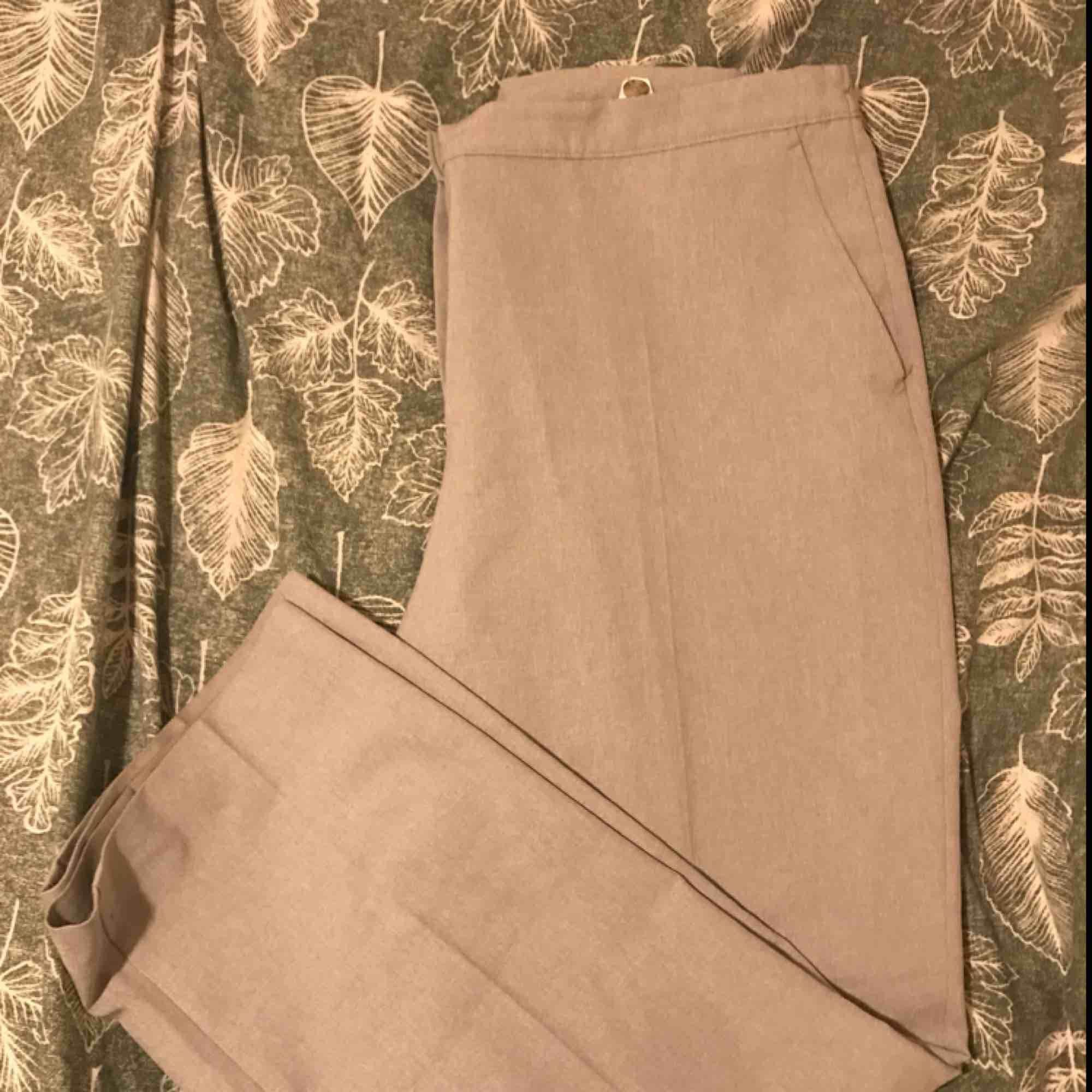 Gråa Kostymbyxor, lite för stora för mig.  Skulle säga att det är en storlek XL.  . Jeans & Byxor.