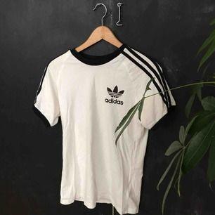 Felfri t-shirt från Adidas som helt enkelt inte används längre! Syns inte helt med bakgrunden men svarta muddar i ärmar och ringning, samt klassiska ränderna längs ärmarna!