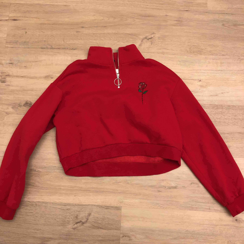 Röd cropad hoodie med en ros på ena bröstet. Nypris 250 men pris kan diskuteras. Köparen står för frakt:)  . Huvtröjor & Träningströjor.