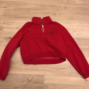 Röd cropad hoodie med en ros på ena bröstet. Nypris 250 men pris kan diskuteras. Köparen står för frakt:)