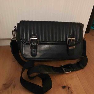 Fin svart väska med likadana fack på vardera sidor. Båda facken har var sitt mindre fack! Fina detaljer och bra skick. Frakt ingår i priset. Swish