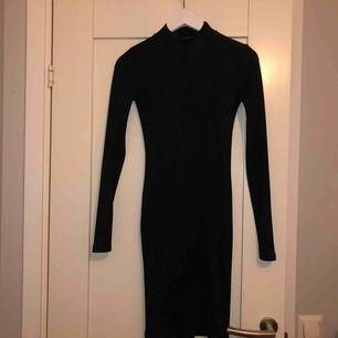 tight svart ribbad klänning från Bubbleroom. Använd 1 gång. Liten krage. Lite liten i storleken. Slutar på knäna.