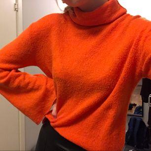 Orange tröja från na-kd med vida ärmar och polokrage.
