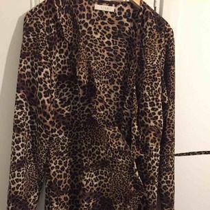 Leopard klänning som man knyter runt midjan med ett snöre, lite volanger på. Använd 1 gång