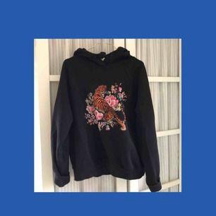 Svart hoodie som passar XS-L, med ett tryck på framsidan
