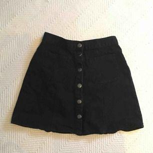 Svart jeanskjol med knappar o fickor framtill! Passar folk som vanligtvis har storlek XS! Frakt: 40 kr
