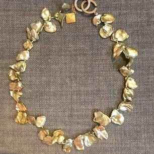 halsband infärgade snäckskal i grön/guld. 45 cm långt, jag skickar med en förlängningskedja. såldes dessa smycken i min affär. skickat mot porto