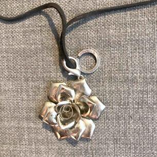 halsband med hänge: blomma i silverfärgat material. löstagbart hänge o man kan reglera längden  säljer då jag har så mkt smycken från min dåvarande butik  skickas mot porto