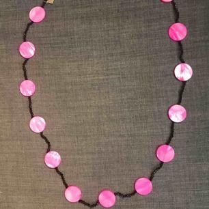 långt halsband med rosa snäckskal och svarta agater . vira det så många varv runt halsen så det känns bra. säljer då jag lagt ned min butik  skickas mot porto