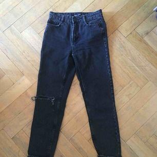 Jättefina svarta mom jeans i storlek 32 från Bershka med hål på ena knät