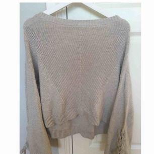Stickad begie tröja från Hollister, används inte längre men väldigt fin. Har utsvängda armar och även snörningar på båda armarna