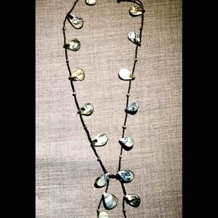 långt halsband med infärgade snäckskal o svarta pärlor. köpt på mallorca. säljer då jag har för mycket smycken.  skickar mot porto
