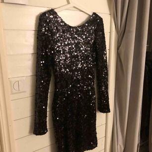 En svart glittrig klänning från Nelly.com. ANVÄND 1 GÅNG! Klänningen slutar ungefär under knäna för mig som är 168cm. Klänningen har svarta lite större paljetter och har en djup rygg där bak. Passar väldigt bra till fest/nyår!