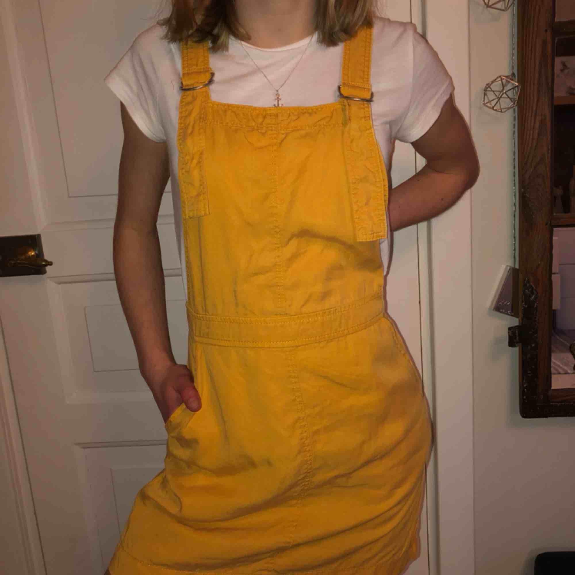 Jag säljer min fina gula hängselklänning i härligt material från bershka. Fint skick! Köparen står för frakten.. Klänningar.