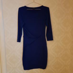 Mörkblå klänning i glansigt tyg och snygg detalj i midjan. Använd några ggr men i fint skick. Frakt ingår.