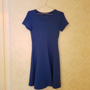 Helt ny oanvänd mörkblå klänning i stl S. Klänningen är klockad nertill och har ett svagt mönster i tyget. Frakt ingår.