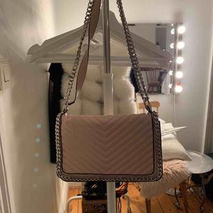 En väska ifrån ginatricot! I bra skick. Ljusrosa men silver kedjor.