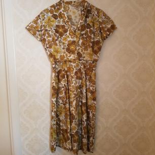Klänning från 60-talet med gulbrunt mönster på vit bakgrund. En liten jacka i samma tyg, som kan stängas med två små dolda tryckknappar, ingår. Jättefint skick på bägge! Frakt ingår.