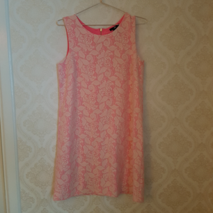 Äldre klänning från HM i 60-talsstil. Jättefint skick. Passar även M då det är en rak modell. Undertyget är rosa med vit spets utanpå. Dragkedja i nacken. Frakt ingår!