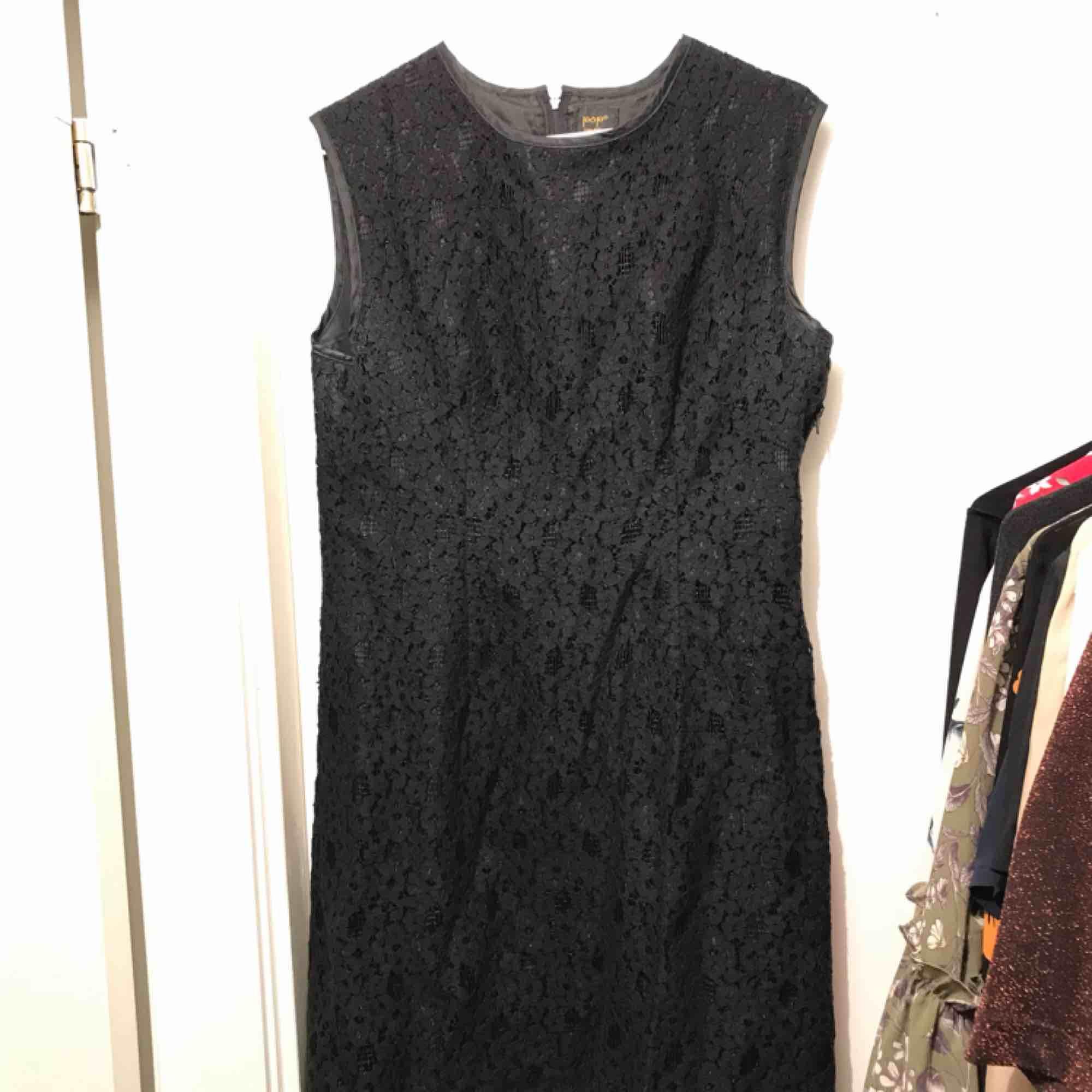 Klänning i svart blommönstrad spets (och underklänning). Sparsamt använd och i fint skick. Frakt ingår i priset. . Klänningar.