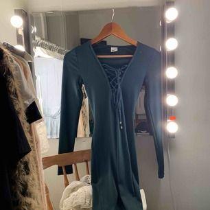 En väldigt fin klänning i mörk grön. Den är tajt och dina former framhävs, vilket gör mycket :)