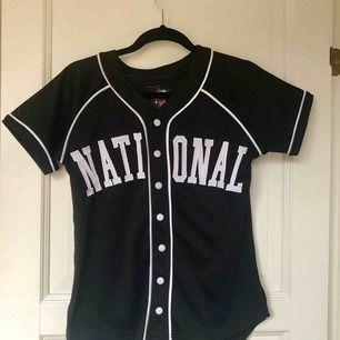 Svartvit baseball t-shirt som aldrig kommer till användning. Köpare står för eventuell frakt!