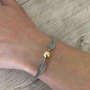 Fint silverfärgat armband med änglavingar och stor guldig pärla i mitten:) symbol från Harry Potter🥰