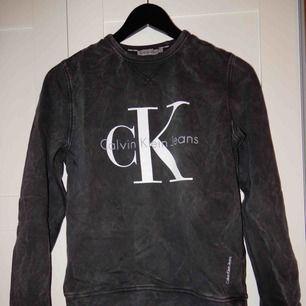 """En helt oanvänd Calvin Klein collage tröja i storlek XS med en """"tvättad"""" grå svart färg, bara att be om bild om ni vill se hur den ser ut på !"""