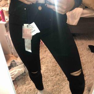 Helt oanvända svarta skinny jeans med hål på knäna. Fin detalj med en pytteliten slits längst ned! Möts upp i Stockholms innerstad eller fraktar (köpare står för fraktavgift).