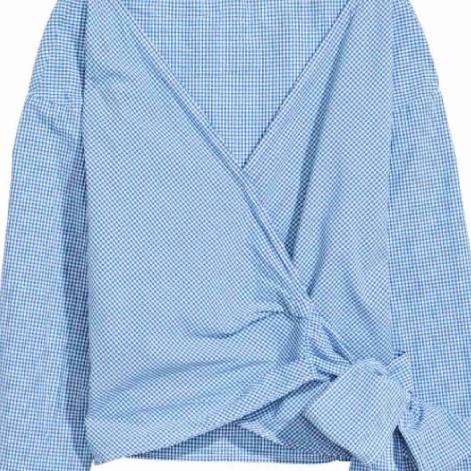 Omlottblus/skjorta från H&M. Vit-blårutig. Knappt använd. Köparen står för ev fraktkostnad ✨. Skjortor.