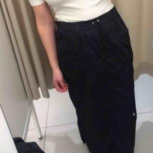 Sportig svart kjol med slitsar längst ner försedda med mesh under. Går att ha öppna eller stänga med dragkedja. Stl 42 men funkar på mig som har XS, man kan dra åt snörena i midjan. Frakt 39 kr.