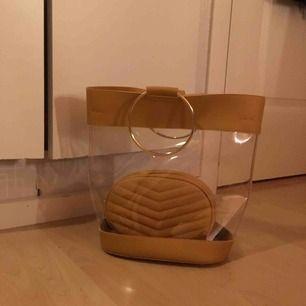 Cool genomskinlig vinylväska med senapsgula och guldiga detaljet och en mindre väska som ingår❣️ köpt på boohoo för ett tag sedan nu men har inte blivit använd mer än 10 gånger, frakt tillkommer!