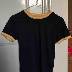 Jättesöt marinblå t-shirt med gula muddar! Den är ganska kort men täcker magen väl. Passar även S om man inte har för störa bröst ;)