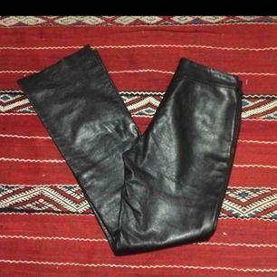 Svarta lätt utsvängda byxor i äkta skinn. Midjemått 80 cm, innebenslängd 85 cm ( men kan lätt kortas). Frakt 63 kr. (Säljer vidare dessa)