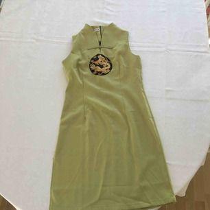 Vacker grön klänning köpt i Kina. Fint guldbroderi av drake. Slits på ena sidan som dock gått upp lite (se bild 3).