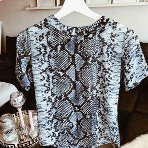 """Blå/ mörkblå/ svart ormmönstrad t shirt i """"genomskinligt"""" material, men man kan ha en vanlig BH under man känner sig inte naken utan det är mest tunt tyg. Passar en XS och S samt en mindre M. Aldrig använd. 🎀"""