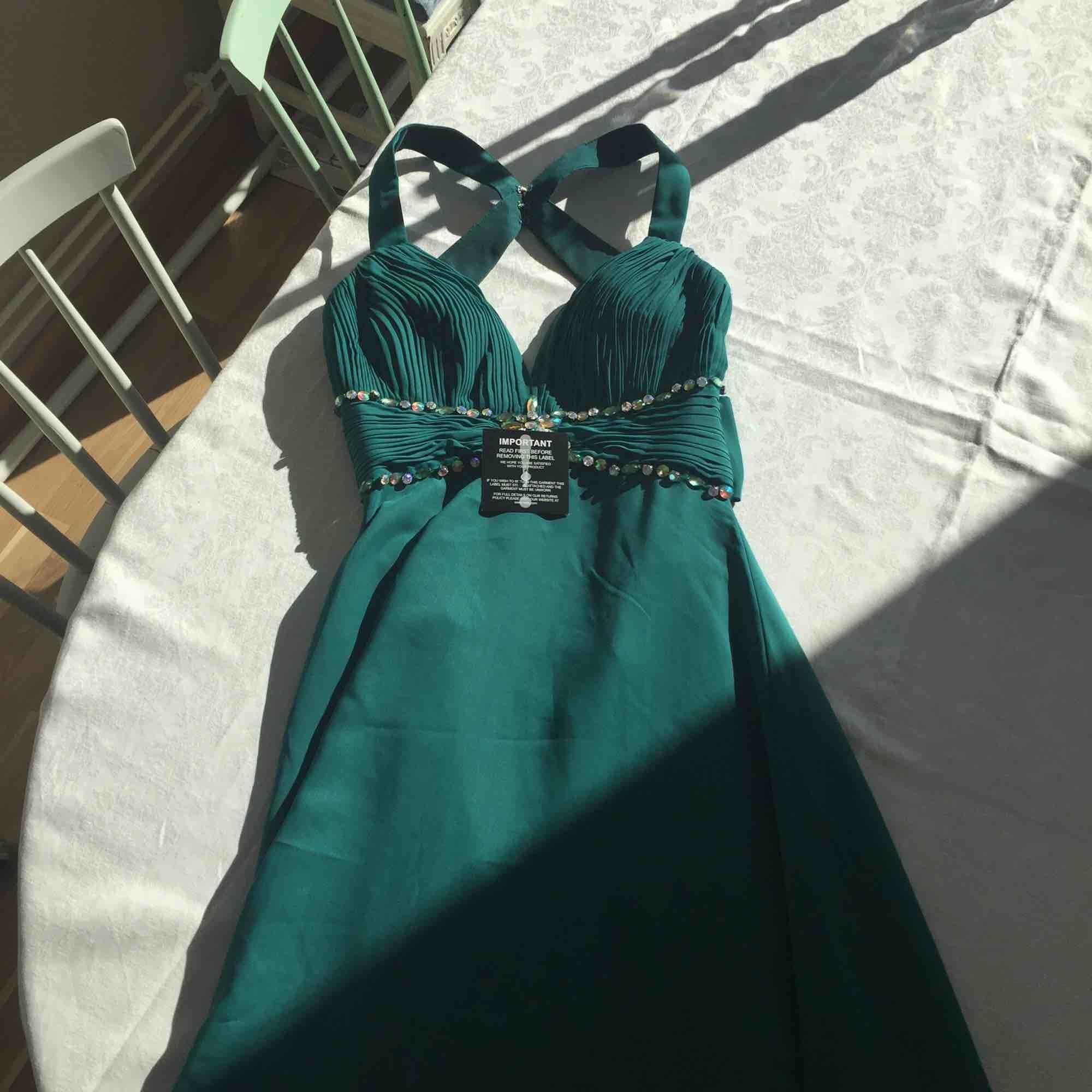 Vacker långklänning i en smaragdgrön färg. Läcker lågskuren rygg och fina stenar. Något längre bak än fram. Oanvänd med lapparna kvar.. Klänningar.