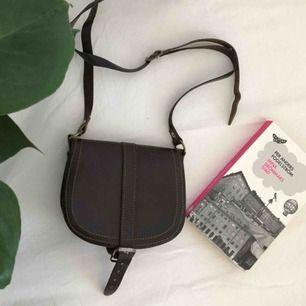Gammal vintage väska i mörkbrunt läder, i fint skick. Se storleken i förhållande till en vanlig pocketbok på första bilden. Axelbandslängd (cm) 98-118. Säljes pga att den inte används längre. Skickas, köparen står för frakt