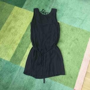 Cool svart klänning med djup urringning i ryggen. Snygga detaljer i urringningen och band i midjan.