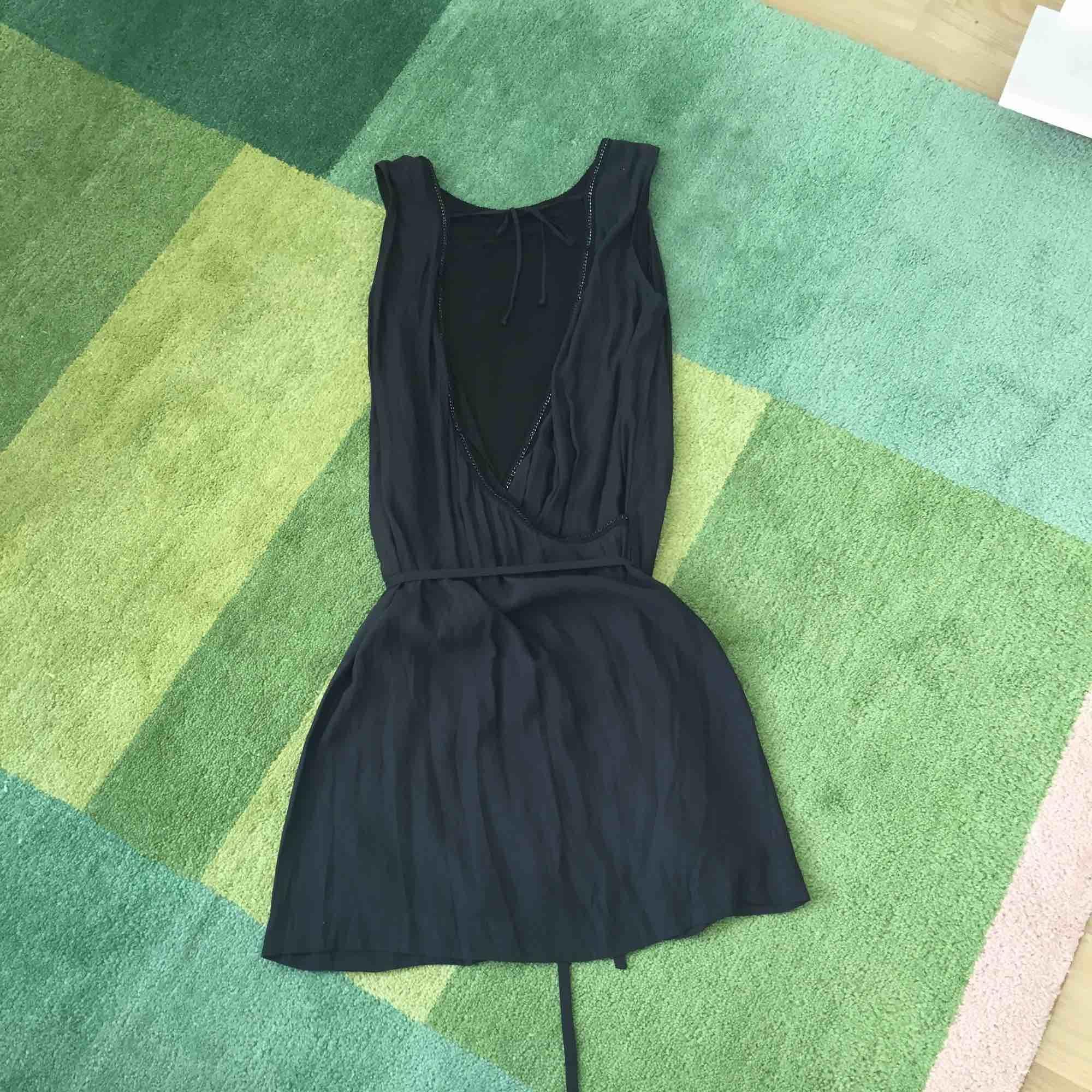 Cool svart klänning med djup urringning i ryggen. Snygga detaljer i urringningen och band i midjan.. Klänningar.