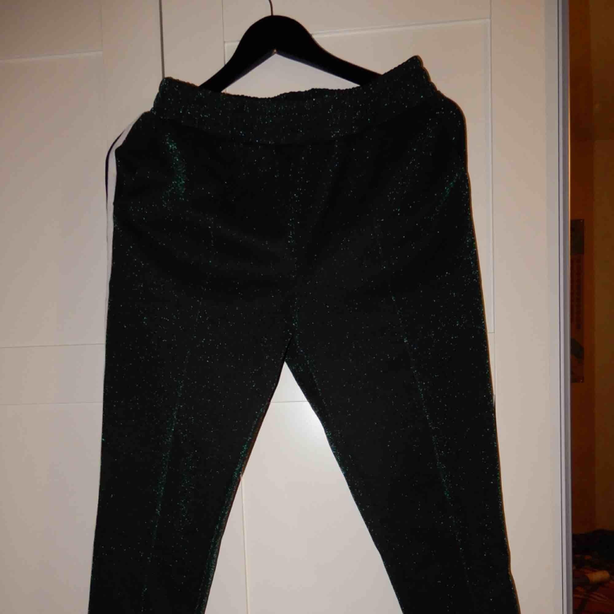 Gröna glittriga byxor med en svartvit rand på sidan, i streschigt material, som sköna kostymbyxor !! Storlek M, endast använda 1 gång. Köpta på Design Only från märket Neo Noir. Jeans & Byxor.