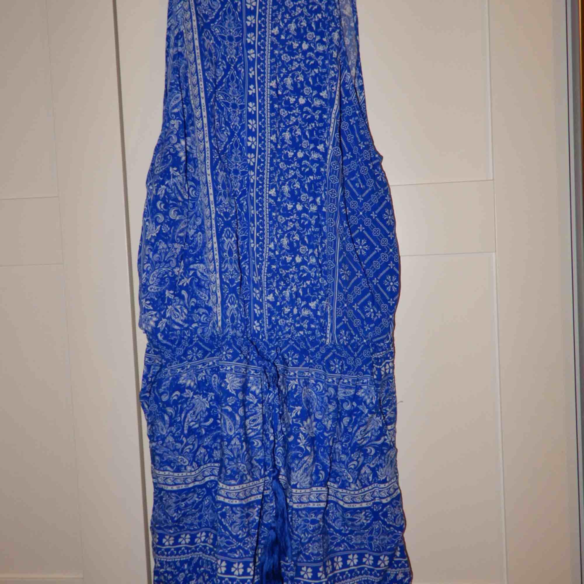 En blå mönstrad jumpsuit, riktigt fin men tyvärr billigt för liten. Öppen i ryggen. Bara att fråga om du vill ha bild hur den ser ut på ! . Övrigt.